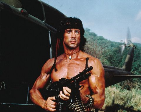 Rambo stands next to a helicopter and is holding a machine gun.