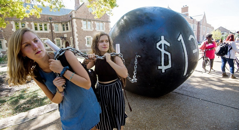 Students pull a mock ball and chain representing the outstanding student debt and price of student loans