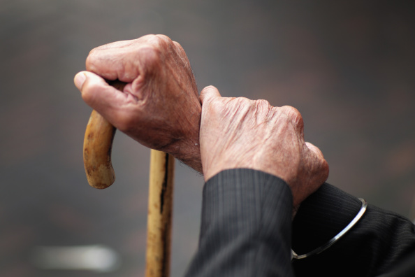 A cane being held by elderly hands.