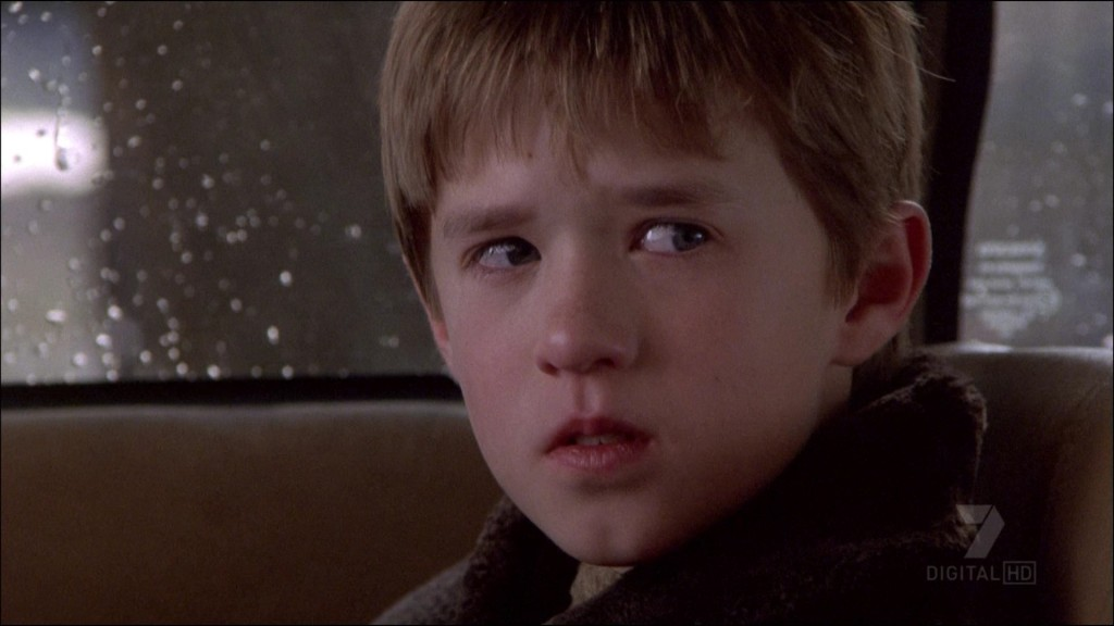 A young Haley Joel Osment sits in the back of a car in The Sixth Sense