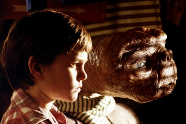 E.T. and Elliott sitting in front of a window.