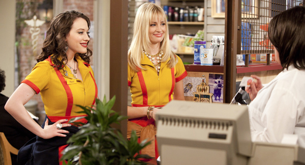 The leads of 2 Broke Girls standing in yellow aprons next to a cash register and smiling