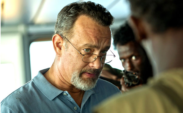 Tom Hanks looks through his glasses at the men invading his ship in Captain Phillips