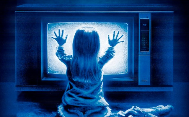 A young girl holds her hands up to a TV in Poltergeist