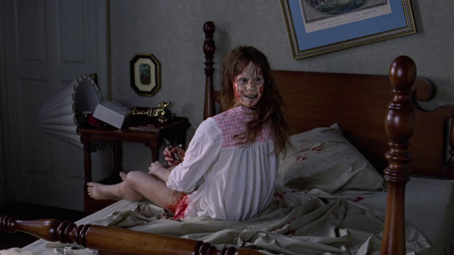 A possessed young girl sits on a bed as her head spins around in The Exorcist