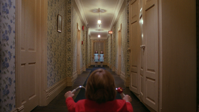 Twins stand at the end of a hallway in The Shining