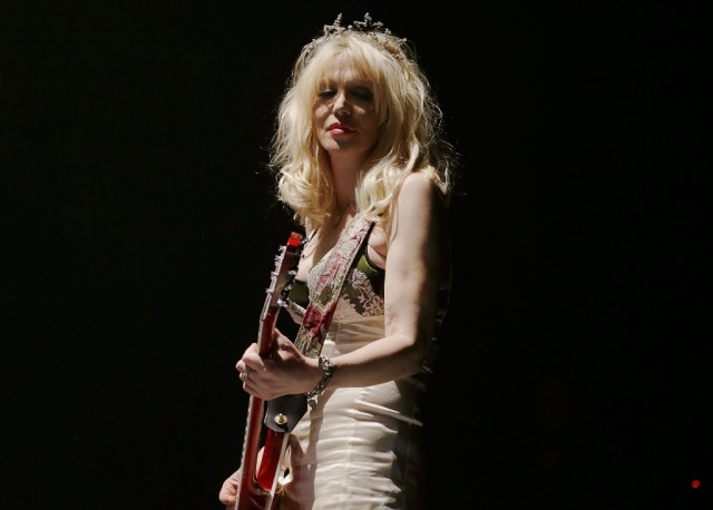 Courtney Love playing a guitar on stage.
