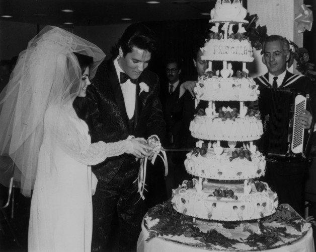 Rock star Elvis and his new wife, Priscilla, cut their wedding cake.