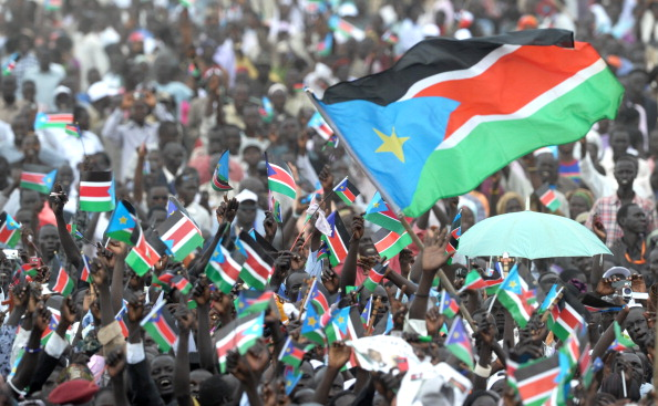 The South Sudanese flag waves above a crowd