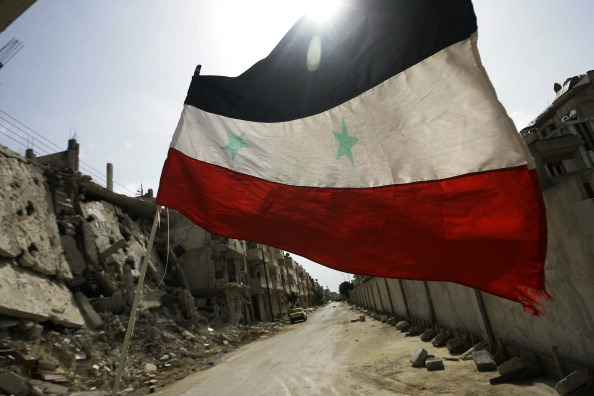 The Syrian flag flies among rubble