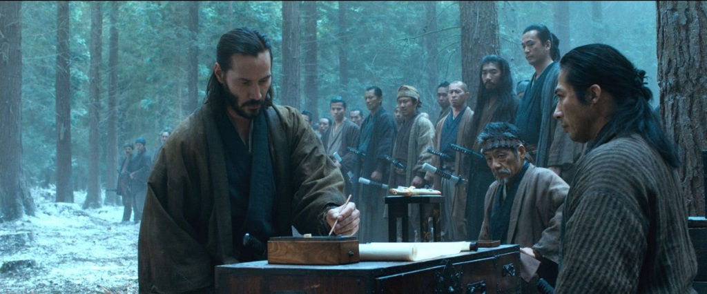 Keanu Reeveswrites something in front of a group of men in the woods in 47 Ronin