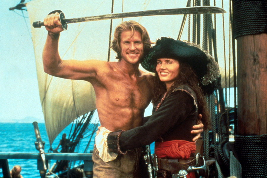A man with his shirt off and a girl dressed as a pirate in Cutthroat Island pose for a photo