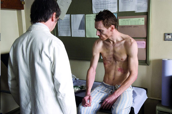 A gaunt, shirtless Michael Fassbender sits on an examination table with a doctor next to hime