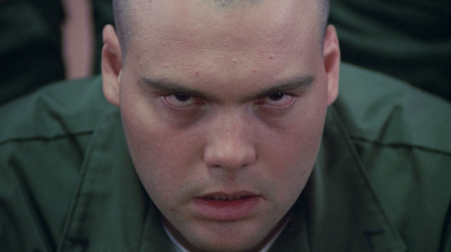 Vincent D'Onofrio in a green shirt, glaring up at the camera
