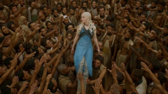 Daenerys Targaryen in a blue dress held up by the hands of a crowd of people in Season 3 finale of Game of Thrones