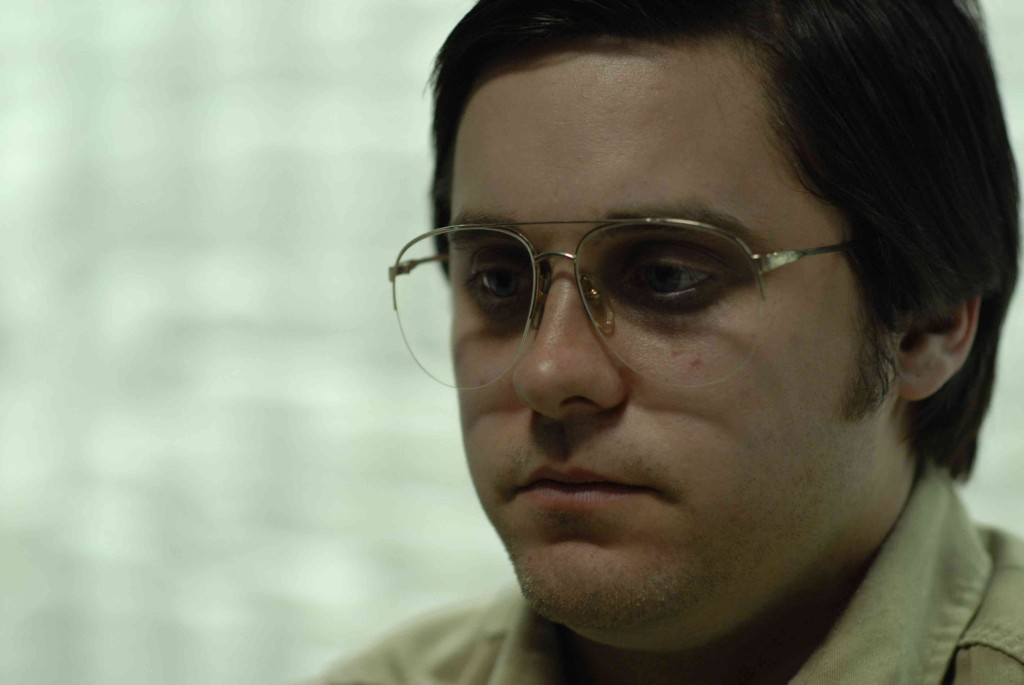 Jared Leto in a fat suit, wearing large glasses and looking to the left of the frame