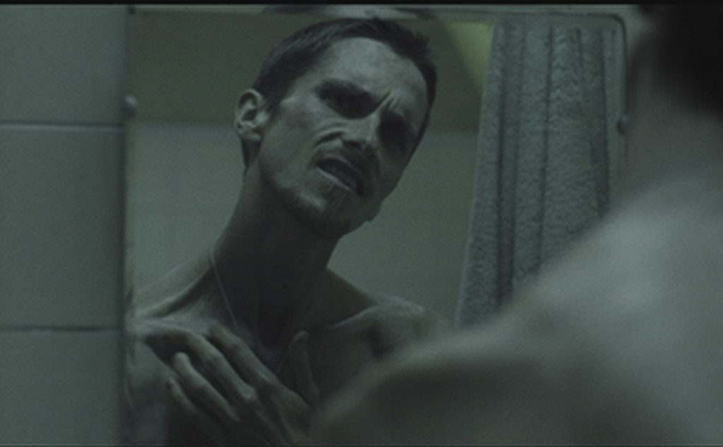 A shirtless, gaunt Christian Bale glowers into a mirror