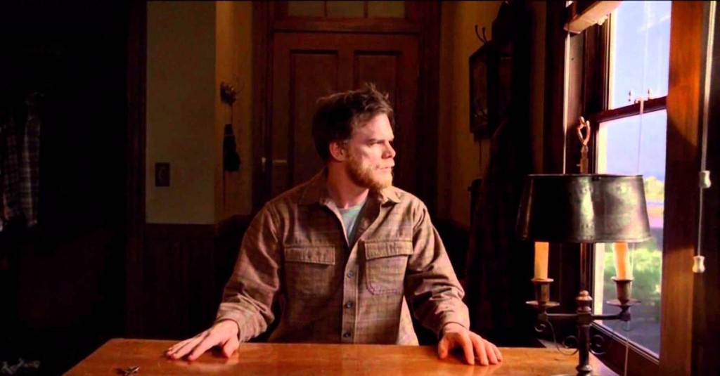 Michael C. Hall as Dexter Morgan sitting at a table in a jumpsuit in the series finale of Dexter