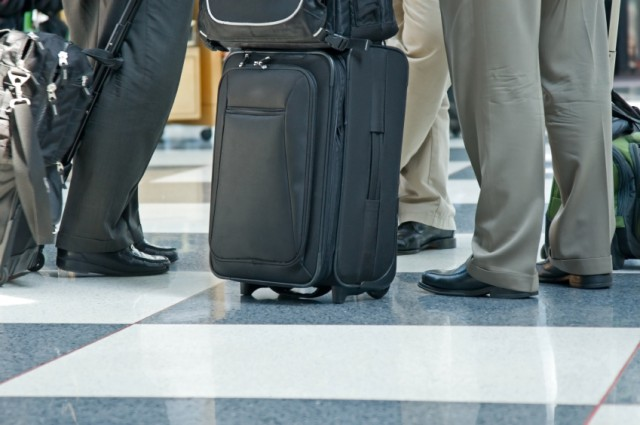 legs of travelers with luggage at airport