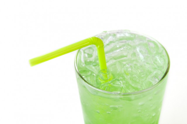 A tall glass full of lime soda and a green straw.