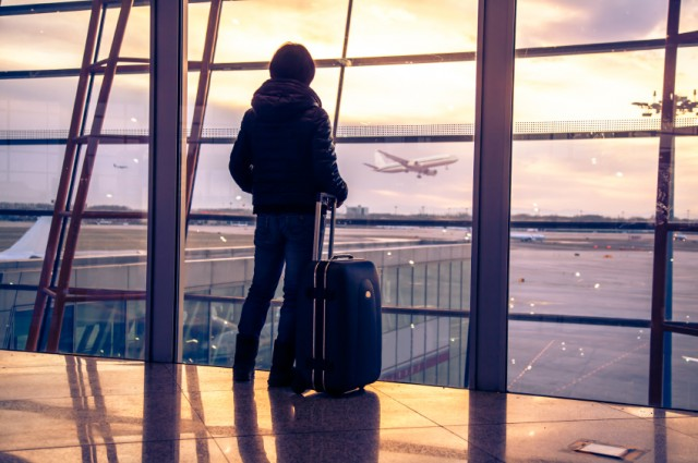 traveler looks out airport window at runways