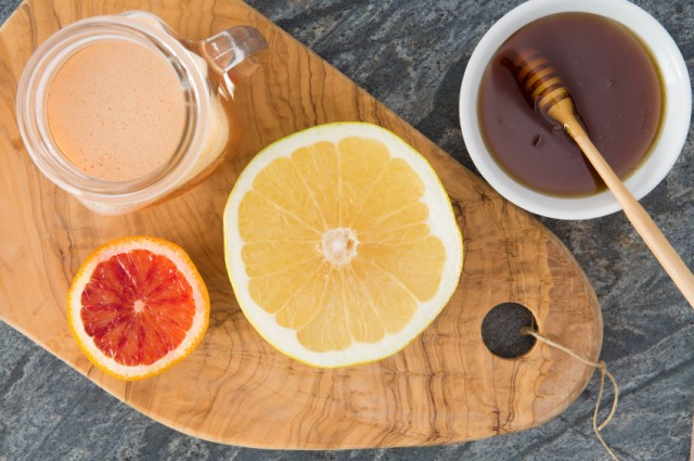 Grapefruit juice, honey, and a wooden board.