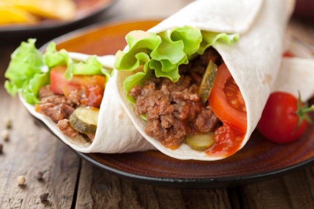Two meat burritos with vegetables served on a plate
