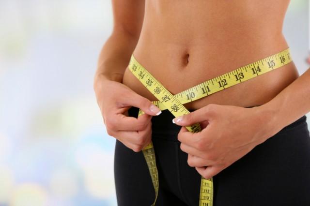 woman taking measurements around her waist