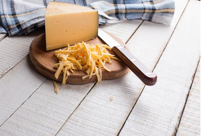 Shredded Gouda cheese on a cutting board