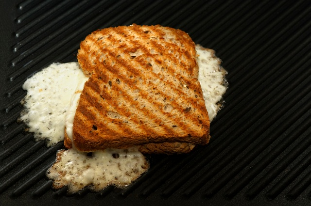 Grilled cheese frying on a griddle