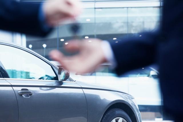 man handing man car keys