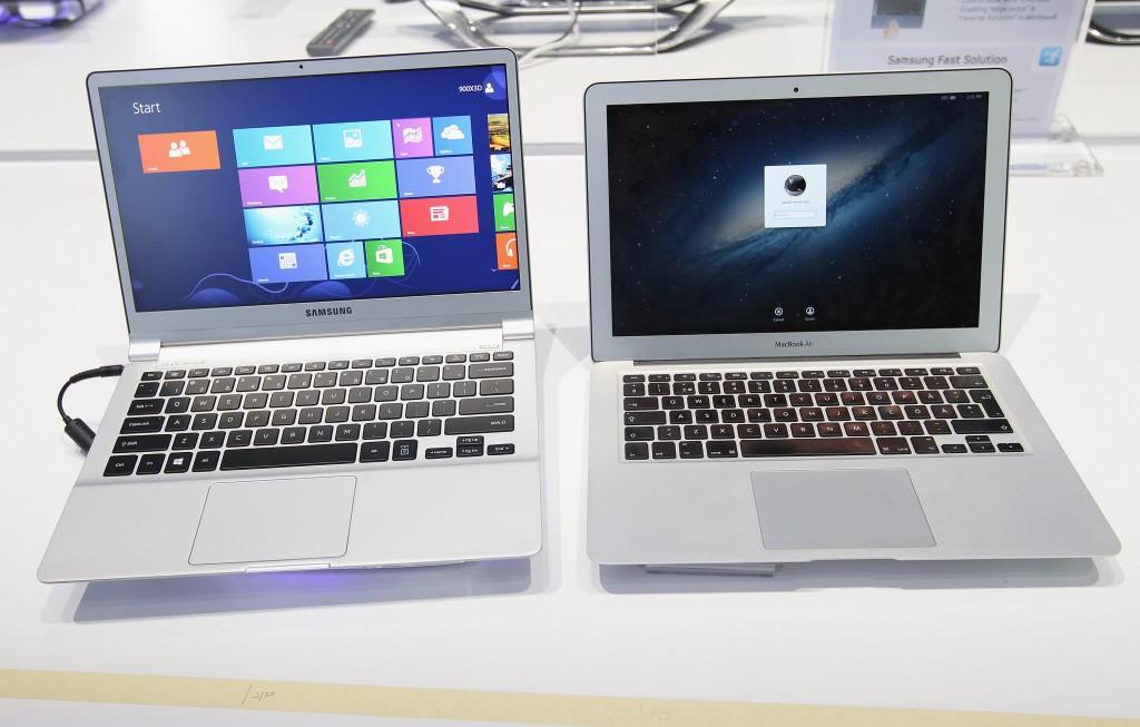 An ultra thin Samsung Notebook Series 9 laptop computer sits next to an Apple Macbook Air.