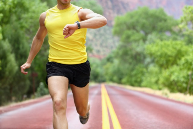 man running and looking at his watch
