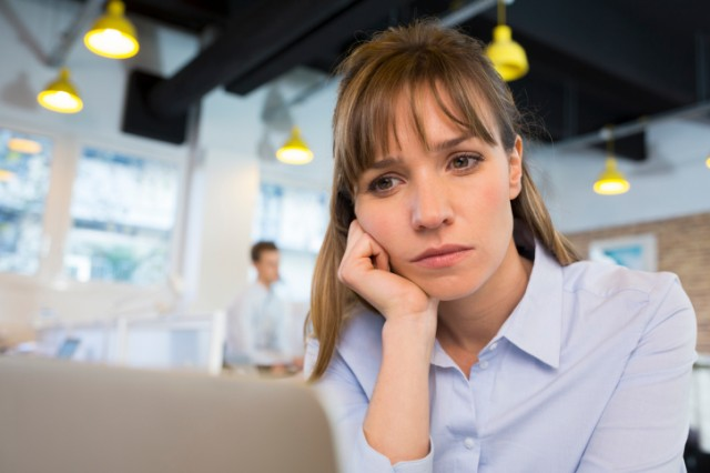 woman looking sadly at her computer