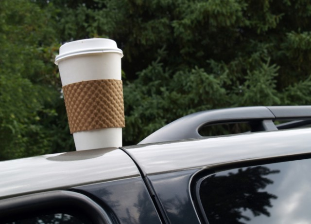 A coffee cup sits atop a car in a parking lot