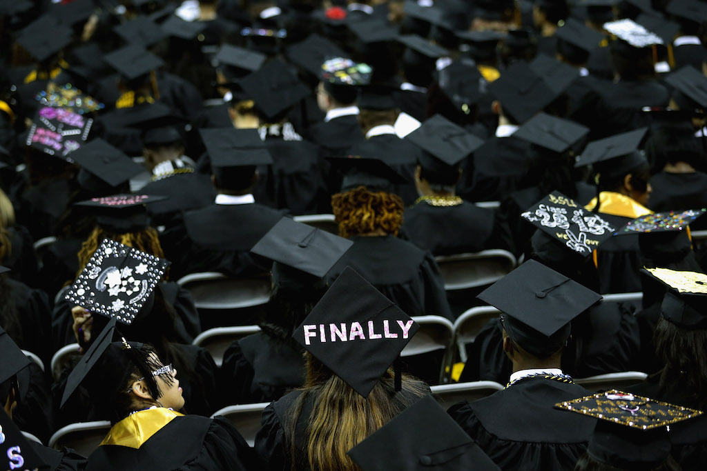 Graduates of Bowie State University put messages on their mortarboard hats during the school's graduation ceremony at the Comcast Center on the campus of the University of Maryland May 17, 2013 in College Park, Maryland. First lady Michelle Obama delivered the commencement speech for the 600 graduates of Maryland's oldest historically black university and one of the ten oldest in the country. (Photo by Chip Somodevilla/Getty Images)