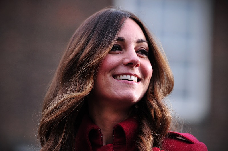 Kate Middleton point she head to the side as she smiles.