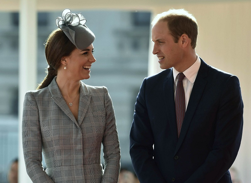 Kate Middleton and Prince William stand next to each other and smile