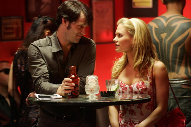 Stephen Moyer as Bill Compton and Anna Paquin as Sookie Stackhouse talking at a table on True Blood