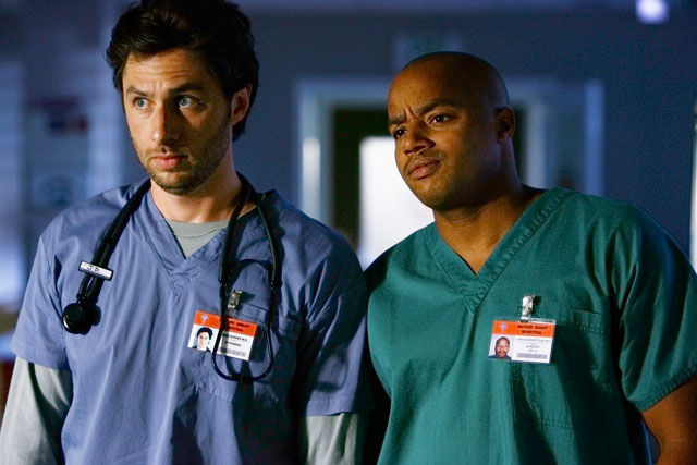 Zach Braff and Donald Fison stand next to each other in hospital scrubs in Scrubs