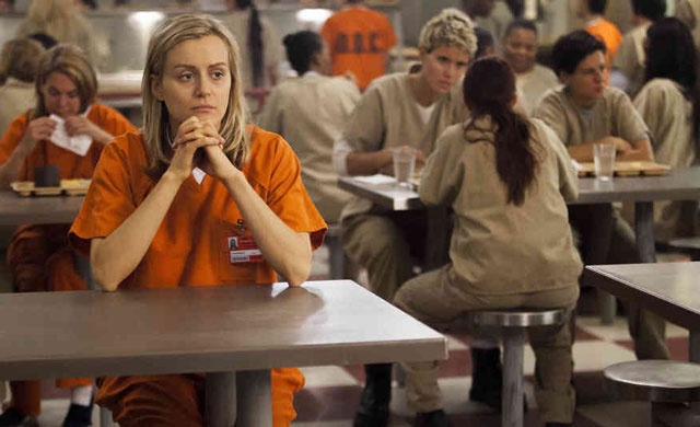 Taylor Schilling clasping her hands and sitting at a table in 'Orange is the New Black.'