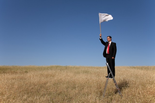 Man holding a white flag on a ladder in a field