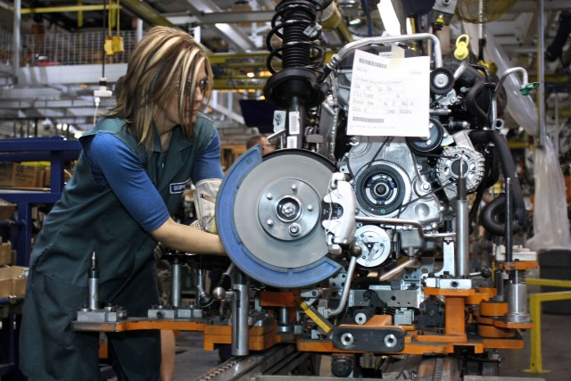A worker builds an engine in a Ford factory