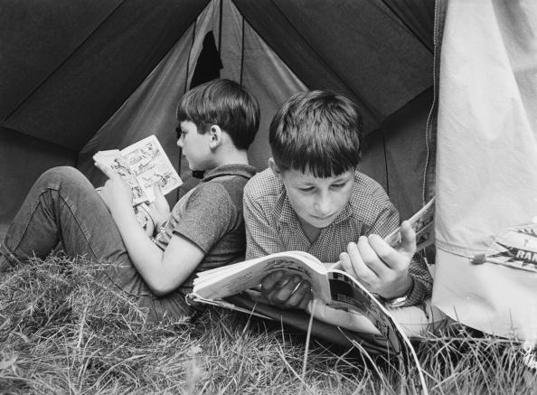 Two young boys reading books