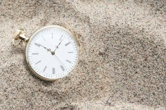 pocket watch sitting in the sand