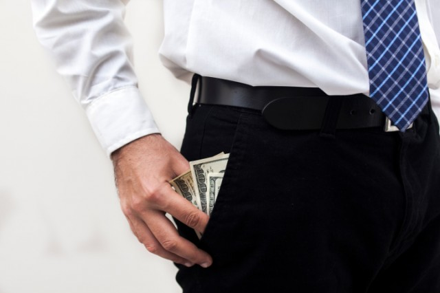 Man with hand in pocket full of money