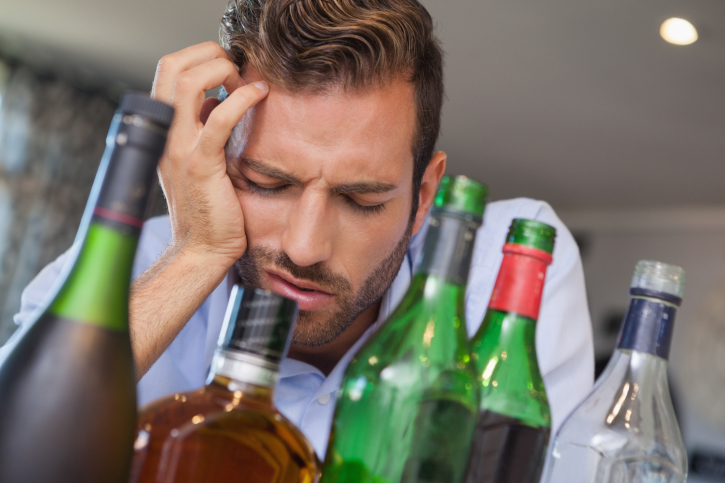 hungover man surrounded by alcohol