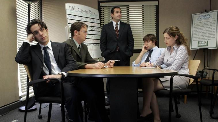 B.J. Novak, Rainn Wilson, Steve Carell, John Krasinski, and Jenn Fischer sitting around a table in a conference room on 'The Office'