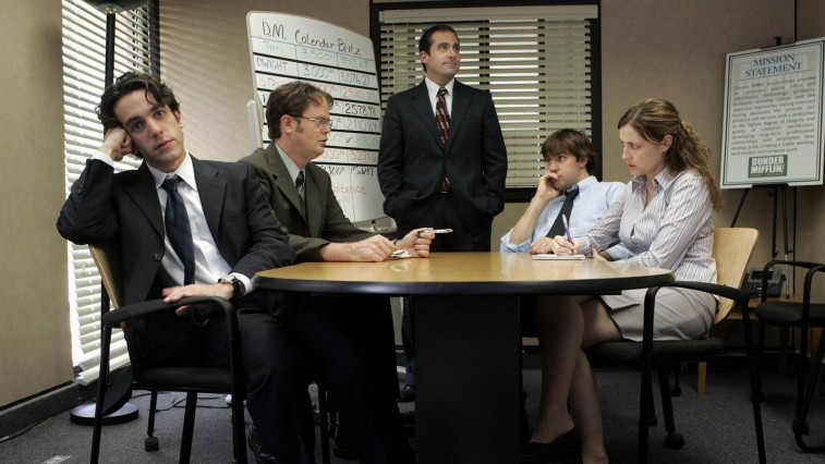 B.J. Novak, Rainn Wilson, Steve Carell, John Krasinski, and Jenn Fischer sitting around a table in a conference room on 'The Office'