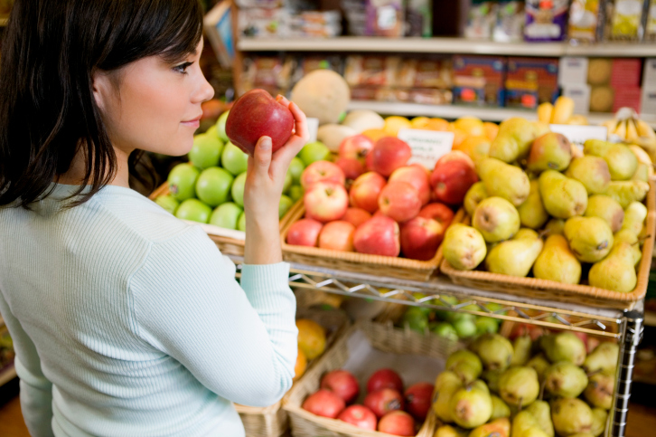 Woman picks up an apple in a grocery store